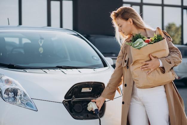 Vrouw met boodschappentassen die elektrische auto oplaadt