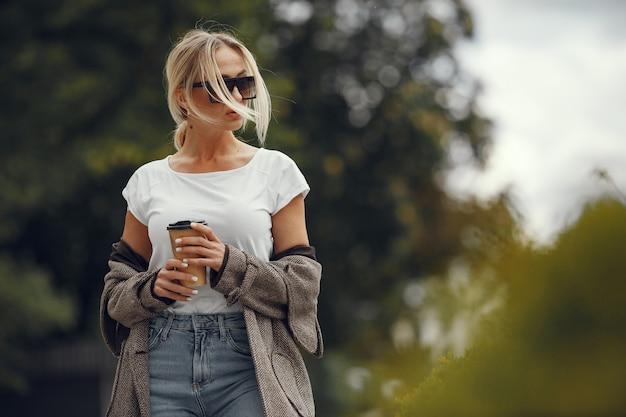 Vrouw met boodschappentassen in een zomerstad