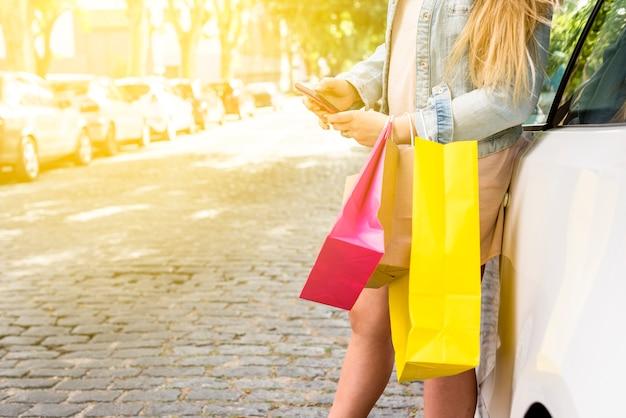 Vrouw met boodschappentassen met behulp van smartphone op auto