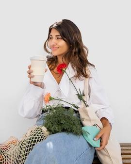 Vrouw met boodschappentassen met koffie buitenshuis