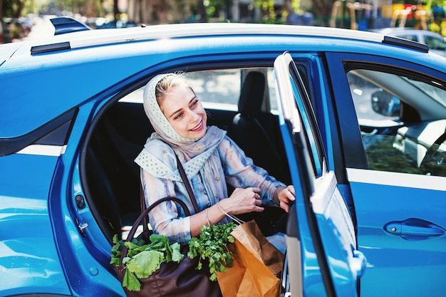 Vrouw met boodschappentassen van de markt zittend op een zakstoel van de auto