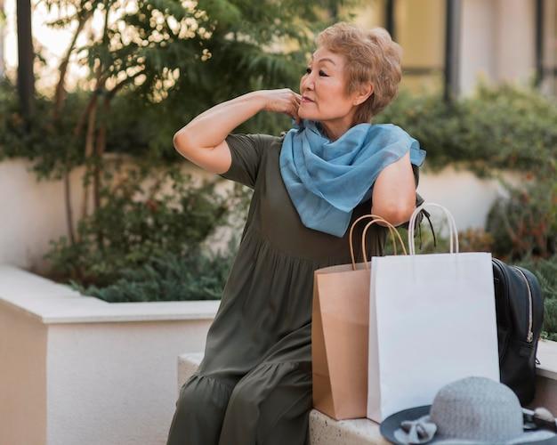 Vrouw met boodschappentassen zitten