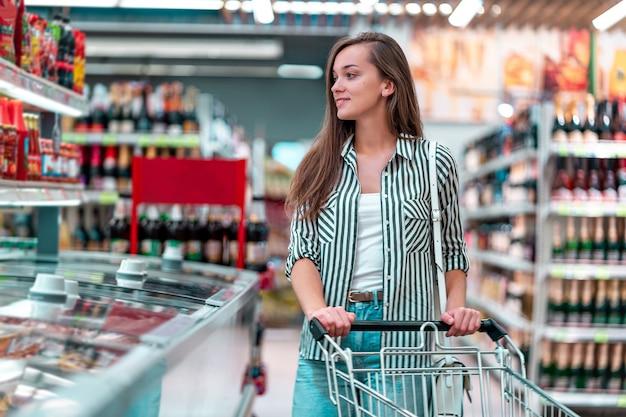 Vrouw met boodschappenwagentje het kopen voedsel bij supermarkt
