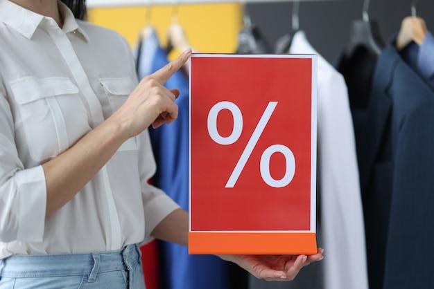 Vrouw met bord met aanduiding van korting in winkel close-up. prijsverlaging concept