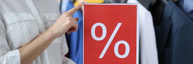 Vrouw met bord met aanduiding van korting in winkel close-up prijsverlaging concept
