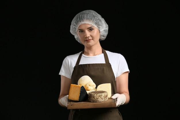 Vrouw met bord met assortiment van smakelijke kaas op donkere ondergrond