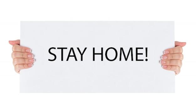 Vrouw met bordje zeg thuis blijven voor bescherming tegen virussen en zorg voor hun gezondheid vanaf covid-19