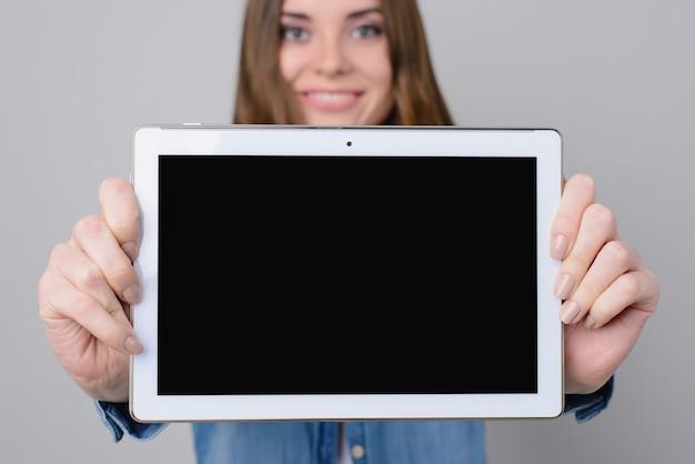 Vrouw met brede glimlach digitale tablet met leeg zwart scherm