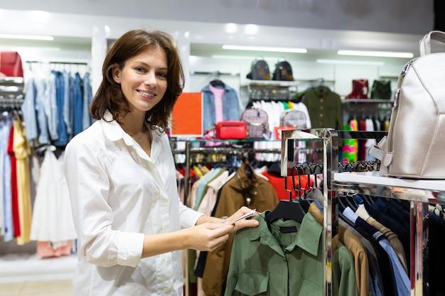 Vrouw met brede glimlach gaat winkelen in winkelcentrum