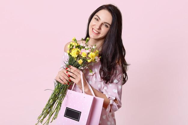 Vrouw met brede glimlach, heeft lang donker steil haar, kantelt hoofd, draagt boeket bloemen en tas met cadeau, poseert op roze, drukt positieve emoties uit, heeft een goede dag