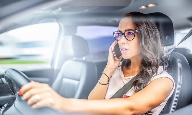 Vrouw met bril die een auto bestuurt, belt op een mobiele telefoon en houdt het stuur met slechts één hand vast.