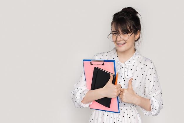 Vrouw met bril die een jurk draagt, gebaart hetzelfde teken