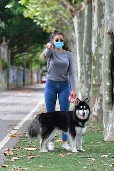 Vrouw met bril en chirurgisch masker met een hond aangelijnd die naar de camera wijst