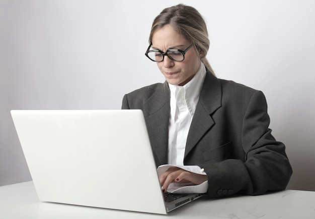 Vrouw met bril en een bezorgd gezicht die op haar laptop op kantoor werkt