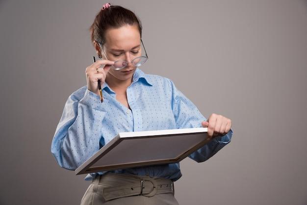 Vrouw met bril met canvas en penseel op grijs. hoge kwaliteit foto
