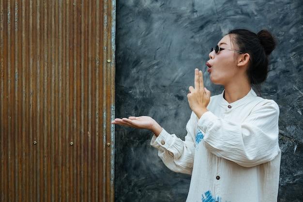 Vrouw met bril staat om te laten zien dat grijs cement en roest rood is.