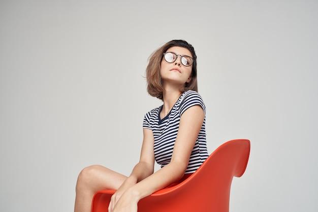 Vrouw met bril zittend op de rode stoel bijgesneden weergave glamour