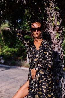 Vrouw met bronzen make-up draagt zwarte gouden jurk en zonnebril in tropisch landschap