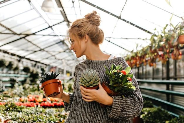 Vrouw met broodje op haar hoofd kijkt naar planten in de winkel en houdt kleine potten met cactus, sappig met en struik met oranje bloemen.