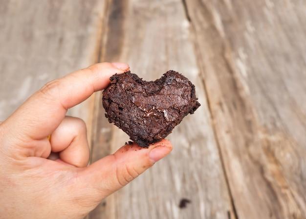 Vrouw met brownie van hartvorm. houten achtergrond.