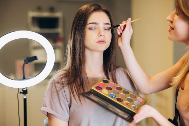 Vrouw met bruin haar en gesloten ogen doet make-up. de visagist brengt glinsterende schaduwen aan op de oogleden.