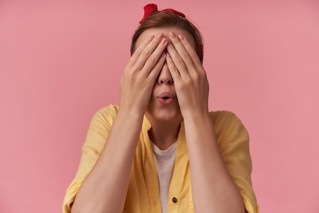 Vrouw met bruin haar met vinger op gezicht oplichter ogen emotie verwarring wow verbergen speelgezicht met rode bandana draagt geel shirt poseren op roze