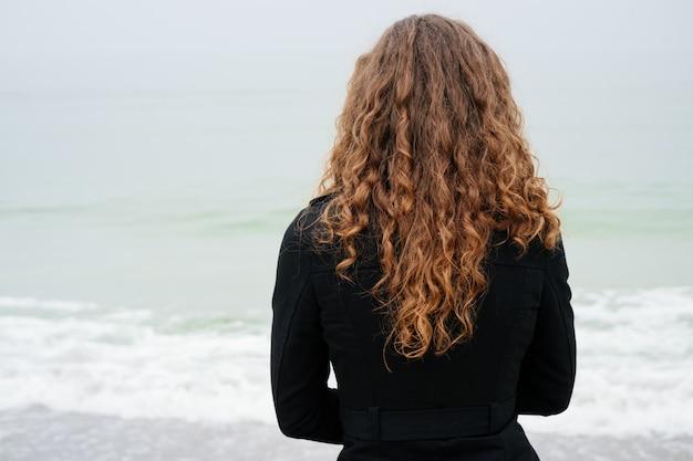 Vrouw met bruin krullend haar in een zwarte laag die het overzees op een bewolkte dag bekijkt