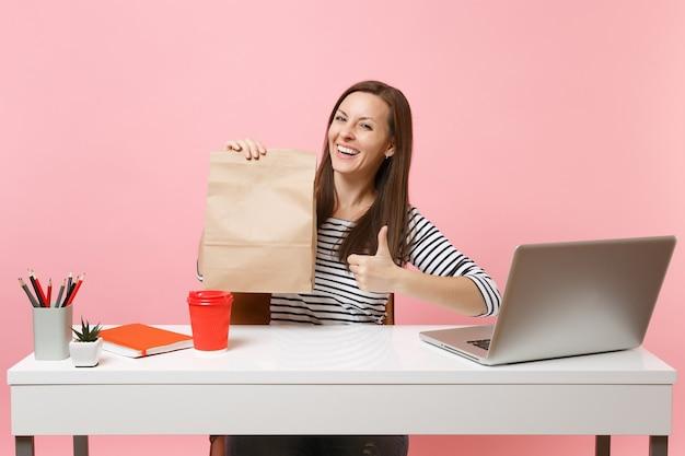 Vrouw met bruine duidelijke lege lege ambachtelijke papieren zak met duim omhoog werk op kantoor met laptop geïsoleerd op roze achtergrond. koeriersdienst voor het bezorgen van voedselproducten van winkel of restaurant naar kantoor.