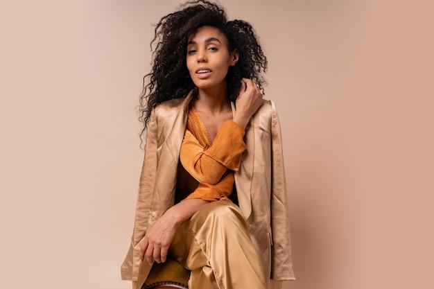 Vrouw met bruine huid met perfect krullende haren in elegante oranje blouse en zijden broek zittend op vintage stoel beige muur.
