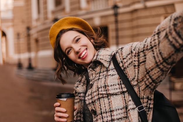 Vrouw met bruine ogen in oranje baret maakt selfie tegen muur van mooi huis