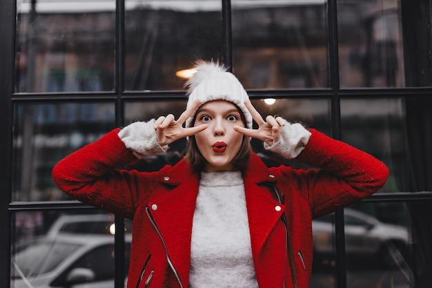 Vrouw met bruine ogen in rode jas, grijze sweater en witte hoed fluit en toont vredestekens tegen raam.
