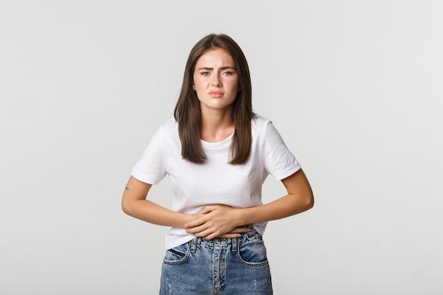 Vrouw met buikpijn, buigen en hand in hand op buik, ongemak van menstruatiekrampen. meisje voelt zich misselijk.