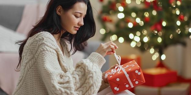 Vrouw met cadeau in de geschenkdoos bij de kerstboom thuis