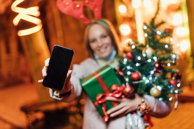 Vrouw met cadeautjes, kerstboom en telefoon met een zwart scherm