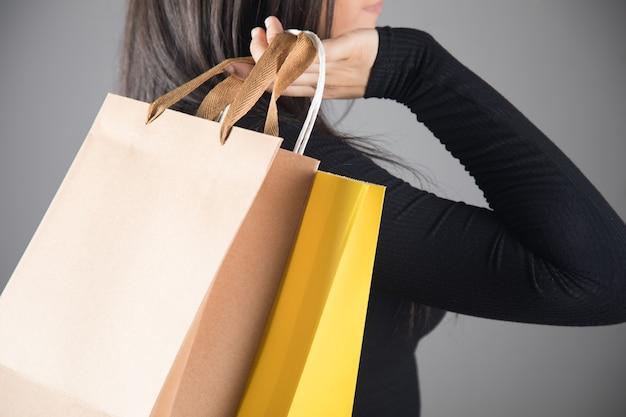 Vrouw met cadeauzakjes op een grijze achtergrond