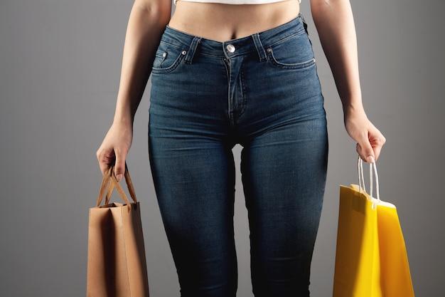Vrouw met cadeauzakjes op grijze achtergrond