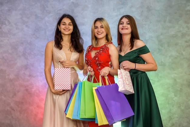 Vrouw met cadeauzakjes op nieuwjaarsfeest poseren in elegante avondjurken