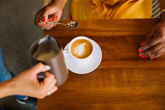 Vrouw met cappuccino-kop op houten lijst