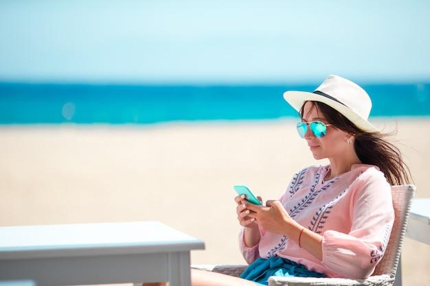 Vrouw met cellphone in openlucht op het strand. toerist met behulp van mobiele smartphone.