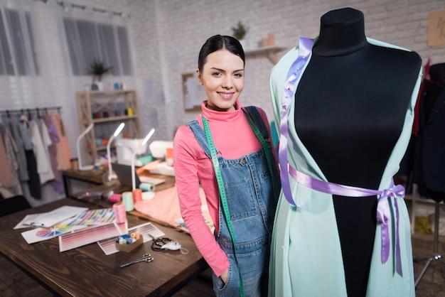 Vrouw met centimeter staat in de buurt van het naaien.