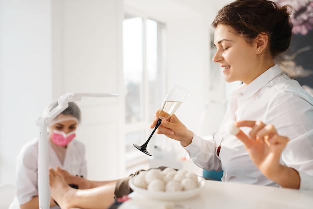 Vrouw met champagne ontspannen in schoonheidssalon, pedicure procedure.