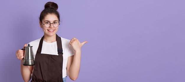 Vrouw met charmante glimlach die een bril, een casual t-shirt en een bruine schort draagt, die opzij met de duim wijst