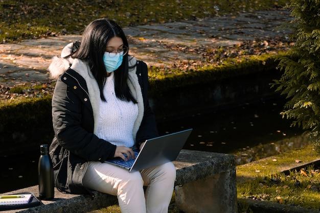 Vrouw met chirurgisch masker dat in het park met laptop werkt. buiten telewerken ivm coronavirus. online business.