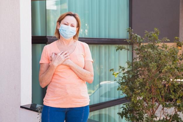 Vrouw met chirurgisch masker op gezicht en hand op hart in dankbaarheid. coronavirus concept