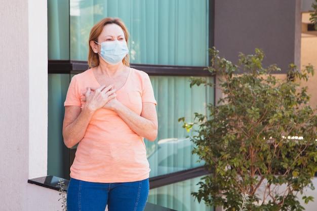 Vrouw met chirurgisch masker op gezicht en hand op hart in dankbaarheid. coronavirus concept Premium Foto