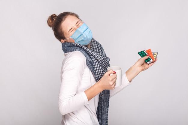 Vrouw met chirurgisch medisch masker, huil omdat ze ziek was. kopje met thee, veel pillen en antibiotica vasthouden. binnen, studio-opname, geïsoleerd op een grijze achtergrond