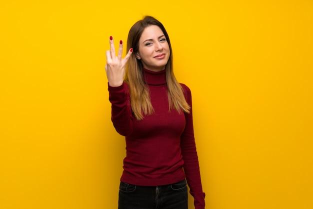 Vrouw met col over gele muur gelukkig en drie met vingers tellen