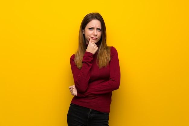 Vrouw met coltrui over gele muur denken