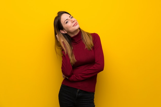 Vrouw met coltrui over gele muur die een idee denkt terwijl het krassen van hoofd