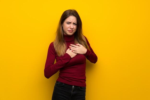 Vrouw met coltrui over gele muur die een pijn in het hart heeft